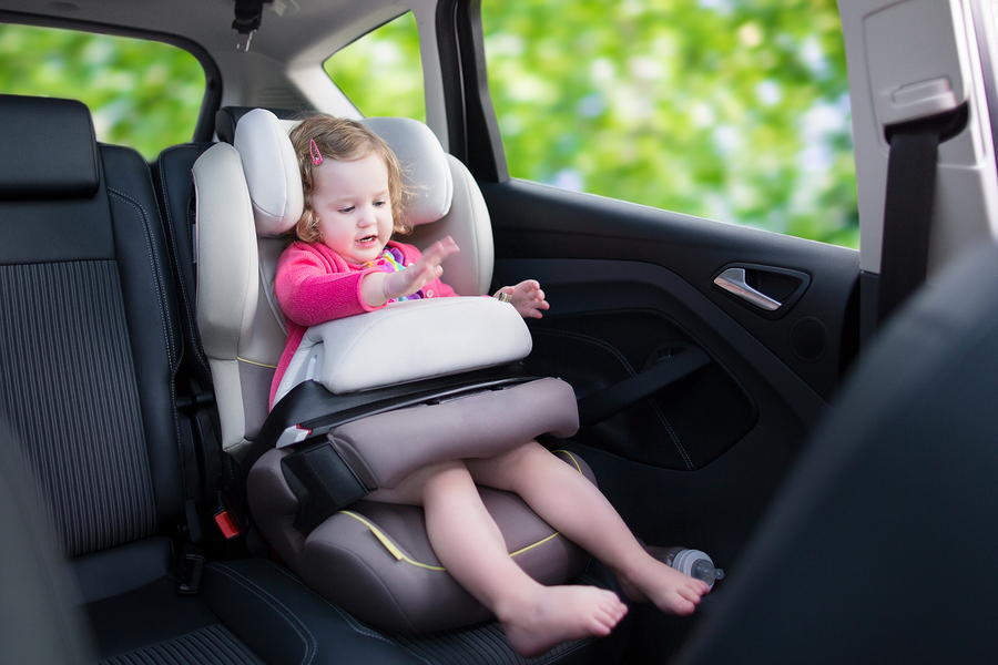 Cute curly laughing and talking toddler girl playing with a toy enjoying a family vacation car ride in a modern safe vehicle sitting in a baby seat with belt having fun watching out of the window